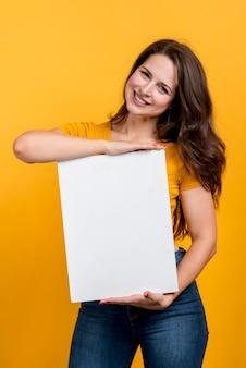 Chica sonriendo mostrando un cartel en blanco