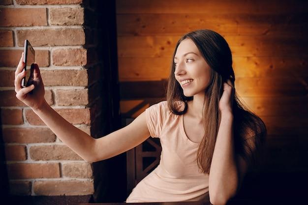 Chica sonriendo tomándose un selfie
