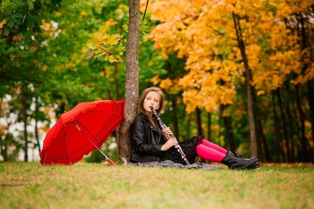 Chica sonriente atractiva joven bajo el paraguas en un bosque de otoño
