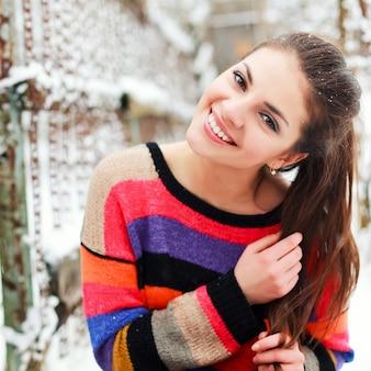 Chica sonriente con cola de caballo y suéter colorido en un día de nieve