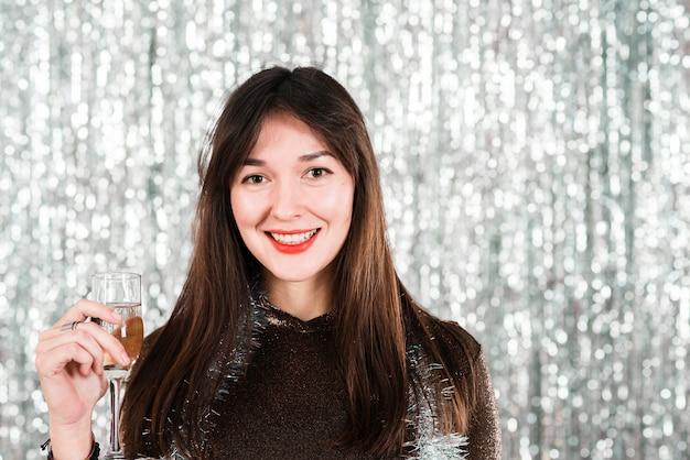 Chica sonriente con copa en fiesta de año nuevo