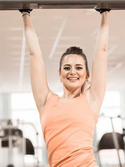Chica sonriente de deporte atlético con cuerpo de forma de fitness posando y relajándose en el gimnasio
