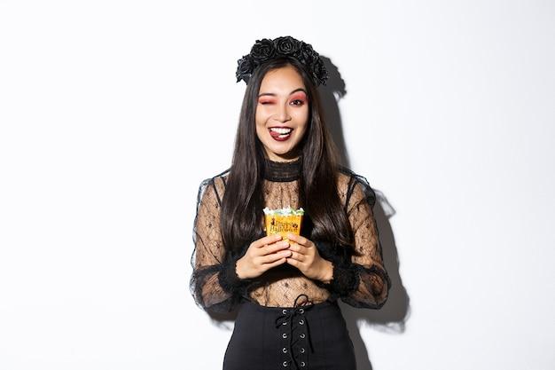 Chica sonriente descarada en traje de bruja, celebrando halloween, haciendo truco o trato con vestido gótico, mostrando la lengua y sosteniendo dulces.