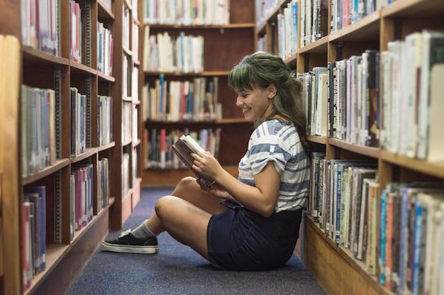 Chica sonriente leyendo en la biblioteca