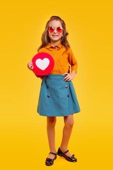Chica sonriente segura de cuerpo completo en traje casual y elegantes gafas de sol que demuestran el icono del corazón