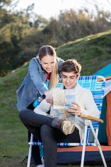 Chica sonriente señalando el mapa de su novio