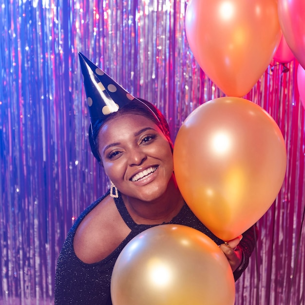 Chica sonriente sosteniendo globos tiro medio