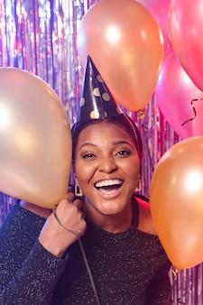 Chica sonriente sosteniendo globos vista frontal