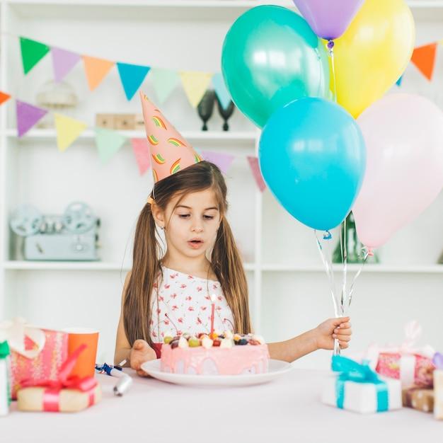 Chica sonriente con una tarta de cumpleaños