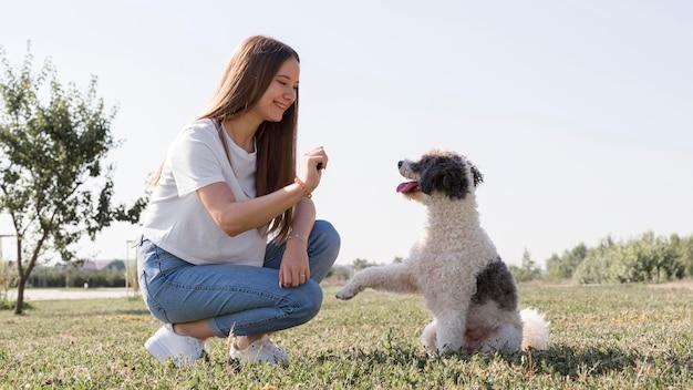 Chica sonriente de tiro completo con lindo perro