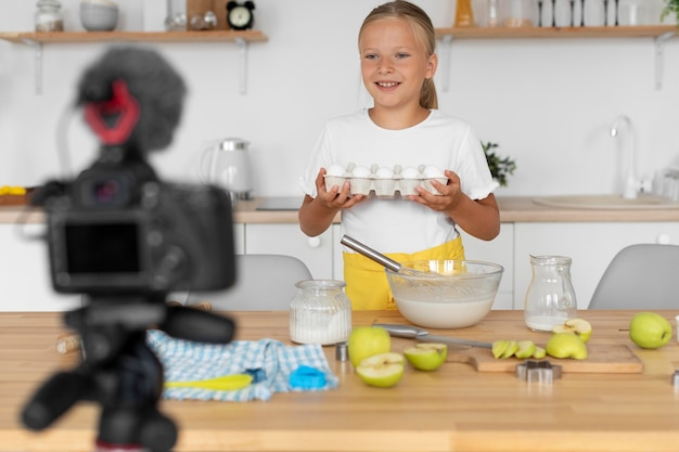 Chica sonriente de tiro medio cocinando