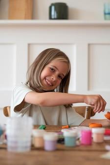 Chica sonriente de tiro medio en el escritorio