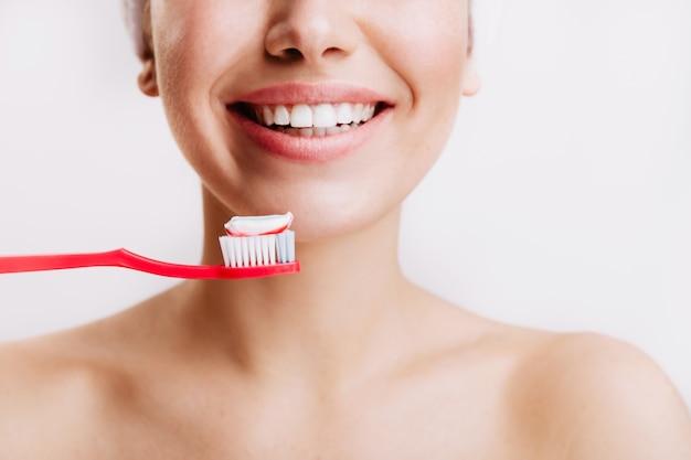 Chica con sonrisa sincera hace rutina matutina y se cepilla los dientes en la pared aislada.