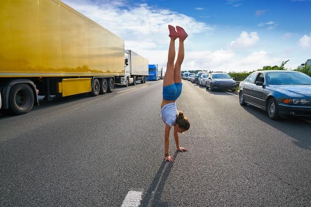 Chica de soporte de mano en una carretera de atasco de tráfico