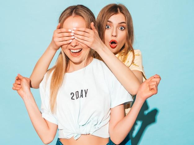 Chica sorprende a su mejor amiga. modelo cubriéndose los ojos y abrazándose por detrás.