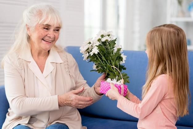 Chica sorprendente abuela con flores y regalo