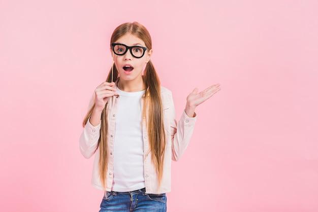 Chica sorprendida con anteojos de apoyo delante de los ojos que se presentan contra el fondo rosa