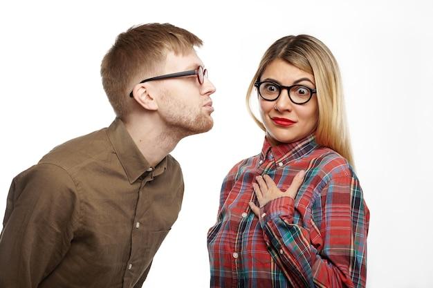 Chica sorprendida con camisa a cuadros de estilo y gafas ovaladas sacando los ojos, sosteniendo la mano en su pecho, sintiéndose aterrorizada mientras un chico nerd la va a besar, haciendo pucheros y cerrando los ojos.