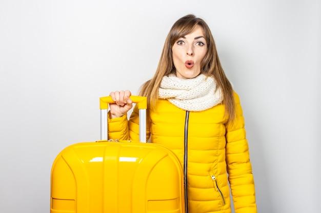 Chica sorprendida en una chaqueta amarilla sostiene el asa de una maleta amarilla