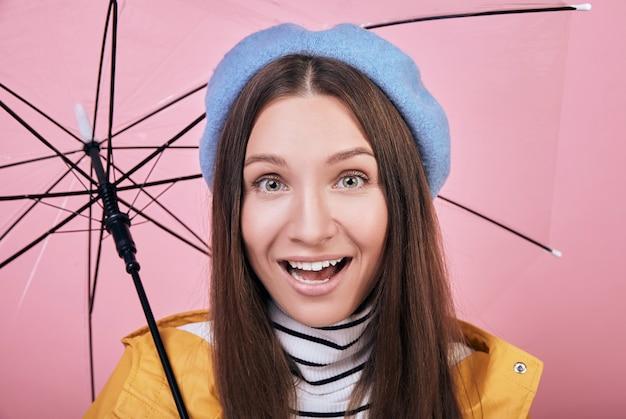Chica sorprendida fresca en chubasquero amarillo con paraguas