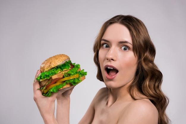 Chica sorprendida por esta hamburguesa de tamaño.