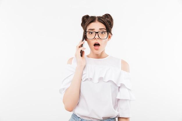 Chica sorprendida o sorprendida con peinado de dos bollos y aparatos dentales en anteojos hablando por teléfono móvil con la boca abierta, aislado en la pared blanca