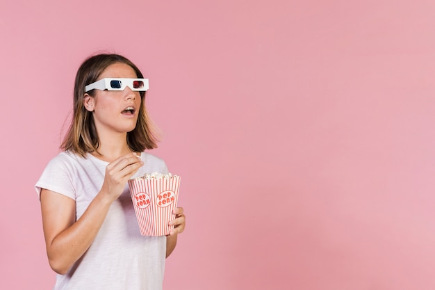 Chica sorprendida con palomitas y gafas 3d