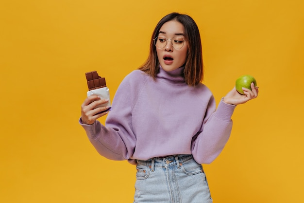 Chica sorprendida con el pelo de camisa en anteojos mira la barra de chocolate con leche