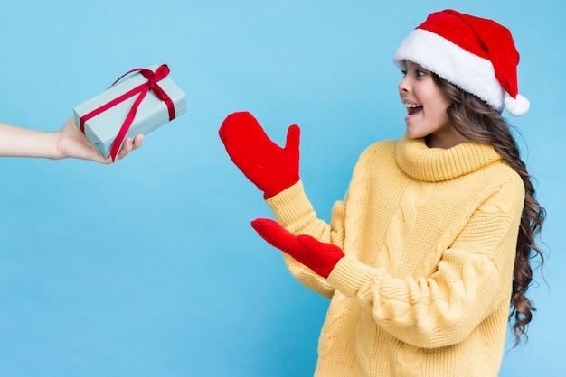 Chica sorprendida recibiendo regalo en invierno