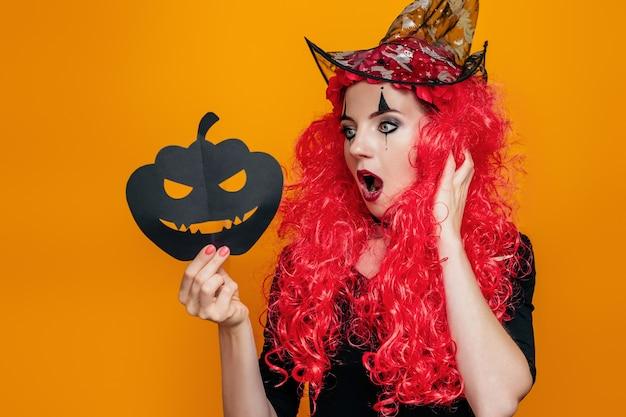 Chica sorprendida sorprendida de halloween sosteniendo una calabaza de papel