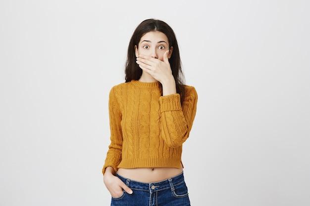 Chica sorprendida y sorprendida jadeando, taparse la boca y mirar con asombro