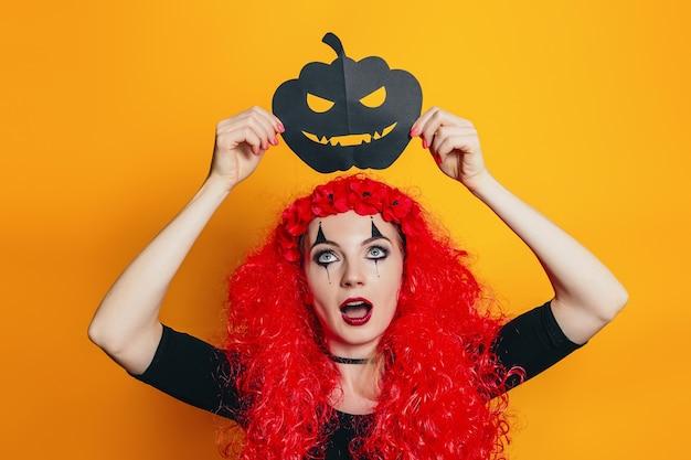 Chica sorprendida sosteniendo papel calabaza de halloween sobre su cabeza
