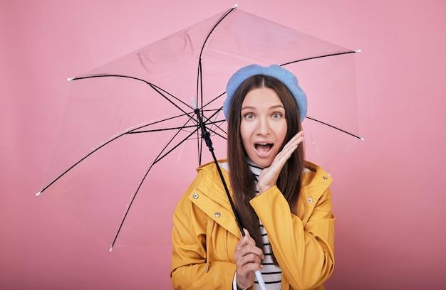 Chica sorprendida en suave boina azul y blusa a rayas con paraguas en manos