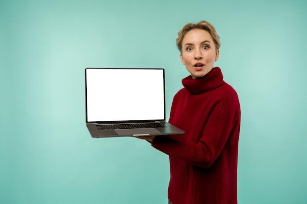 Chica sorprendida con un suéter rojo demuestra una pantalla de portátil en blanco en un espacio azul