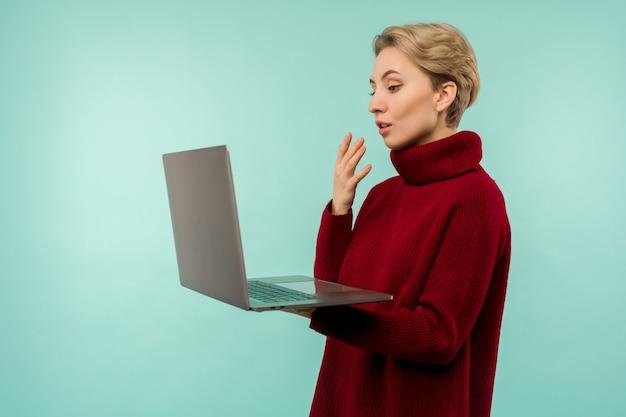 Chica sorprendida con un suéter rojo mira la pantalla de un portátil en un espacio azul