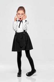 Chica sorprendida en uniforme escolar con la boca abierta y sosteniendo gafas redondas