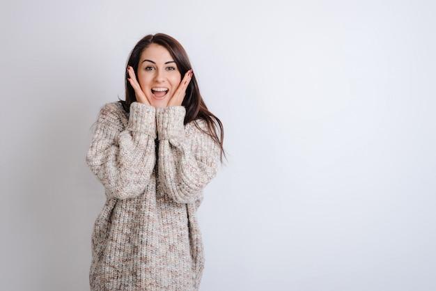 Chica sorprendida vistiendo suéter cálido en blanco