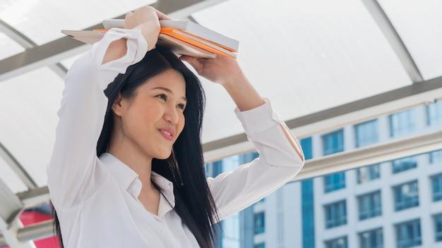 Chica sostenga el libro en la cabeza con sentimiento feliz