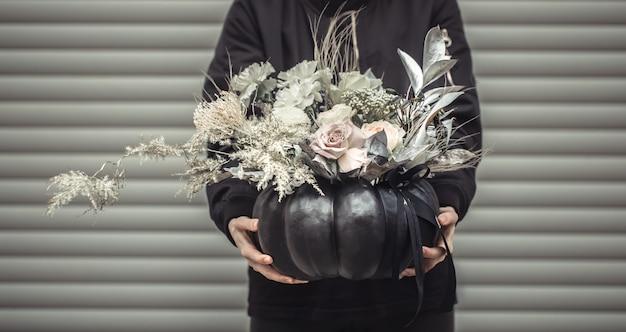 Chica sosteniendo un arreglo floral en una calabaza.