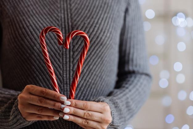 Chica sosteniendo cacao con crema batida y menta bastón de caramelo. navidad.