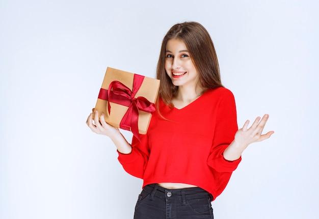 Chica sosteniendo una caja de regalo de cartón envuelto con cinta roja y apuntando a alguien.
