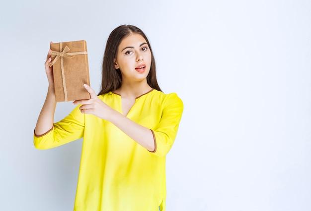 Chica sosteniendo una caja de regalo de cartón y parece confiada o pensativa.