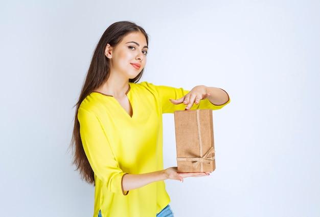 Chica sosteniendo una caja de regalo de cartón y sintiéndose positiva.