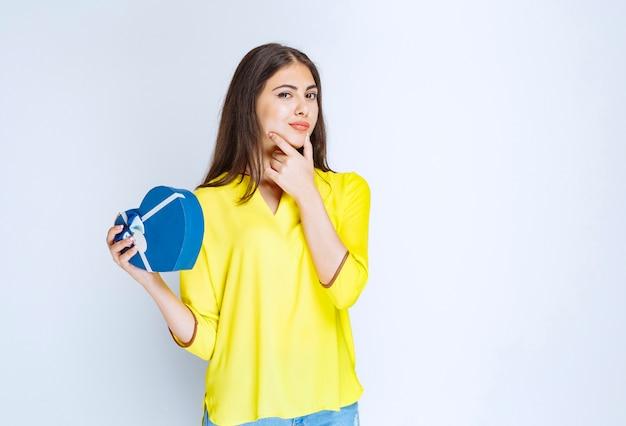 Chica sosteniendo una caja de regalo con forma de corazón azul y pensando o dudando.