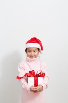 Chica sosteniendo una caja de regalo en suéter y gorro de papá noel