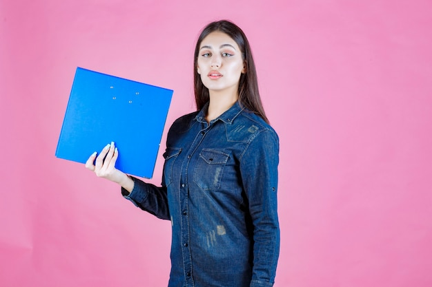 Chica sosteniendo una carpeta de informes comerciales con confianza