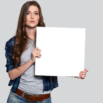Chica sosteniendo cartelera blanca