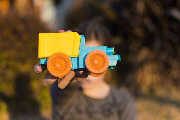 Chica sosteniendo un coche de juguete frente a su cara