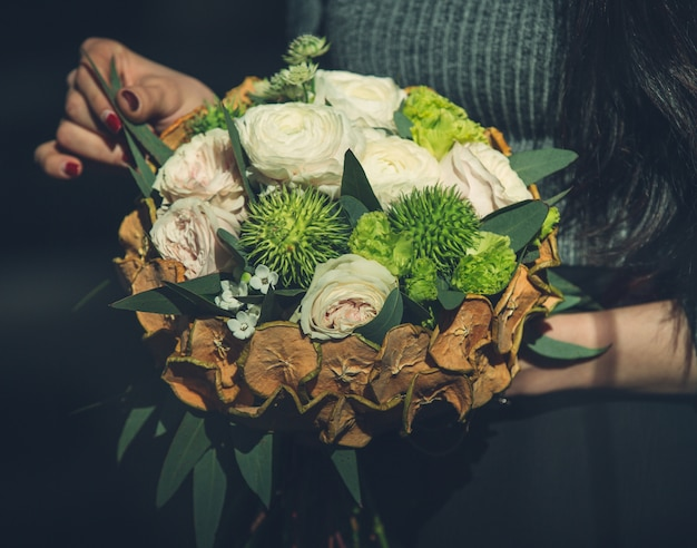 Chica sosteniendo un concepto rústico de navidad bouquet