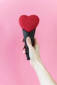 Chica sosteniendo un corazón de punto en su mano en una taza de oblea negra sobre un fondo rosa